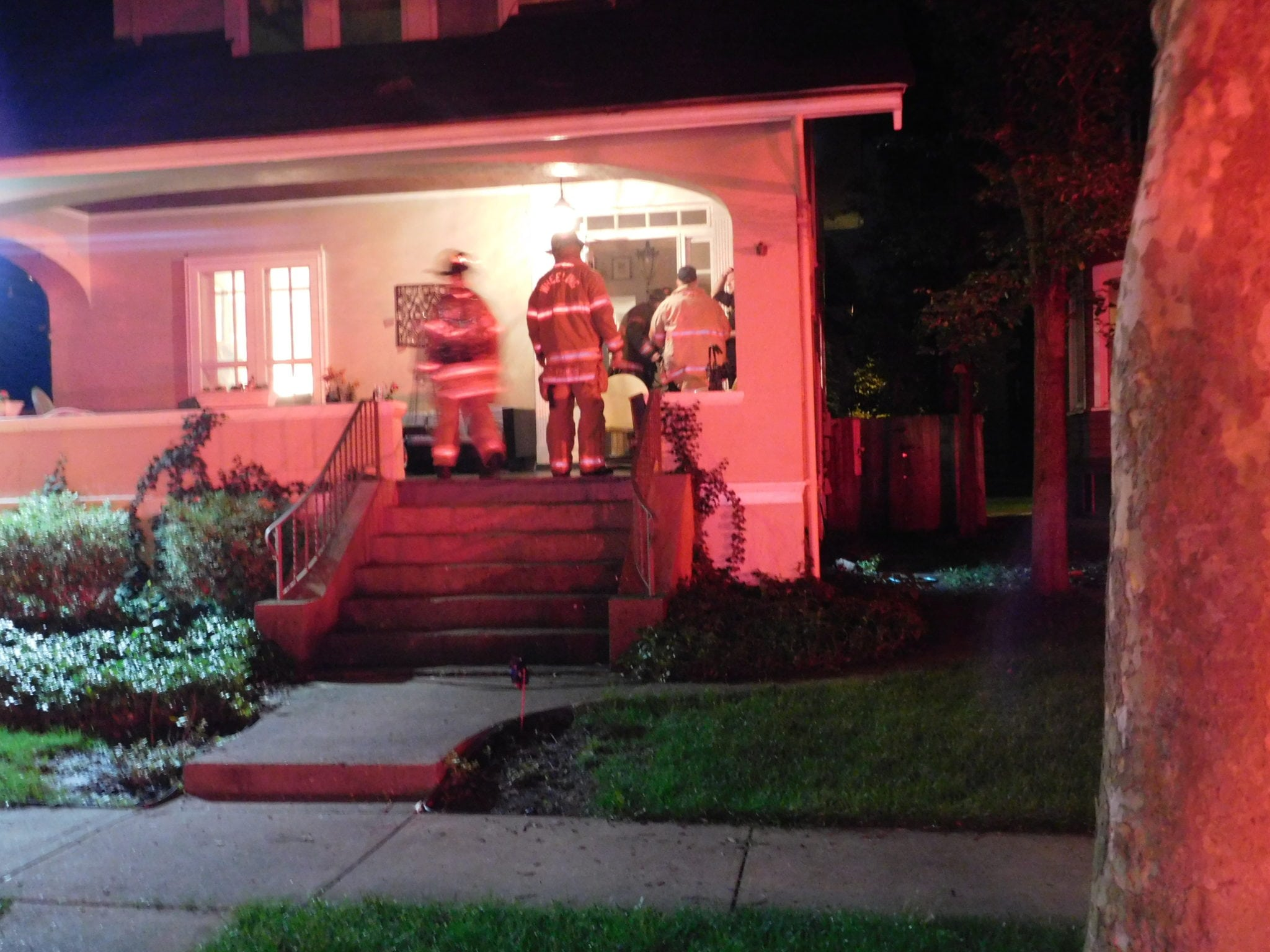 Firefighters on porch of house